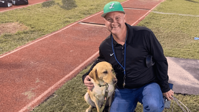 Lafayette High alum Buffy Massey poses for a photo with his dog Nikon before last week's game at the Lion's Den.