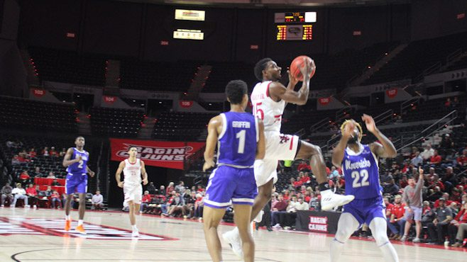 Cajuns guard P.J. Hardy in his first game back going for a layup between two UT Arlington defenders. Photo courtesy of Clint Domingue