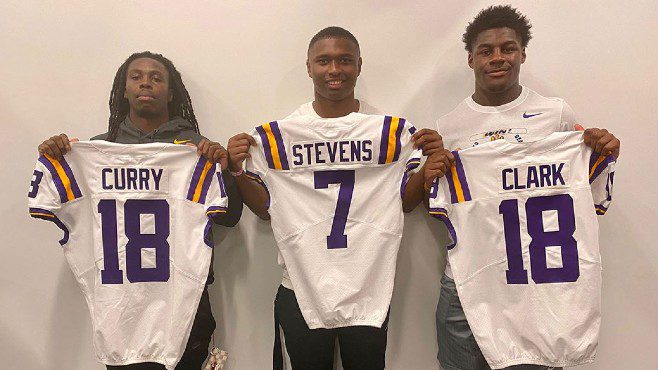LSU running back Chris Curry and linebacker Damone Clark holds No. 18 jerseys while safety Jacoby Stevens holds up a No. 7 jersey. — Photo courtesy of LSU Athletics