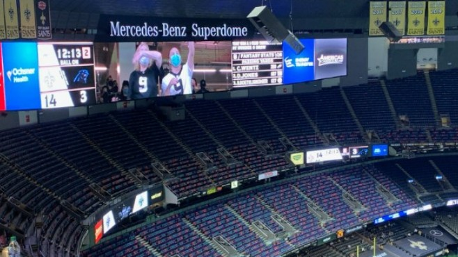 A few fans can be seen cheering on the jumbotron inside a nearly empty Mercedes-Benz Superdome during Sunday's game between the New Orleans Saints and Carolina Panthers. -- Photo by Raymond Partsch III